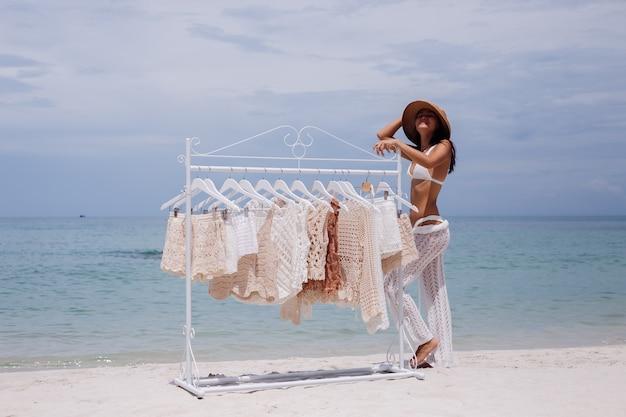 해변에 옷걸이에서 니트 옷을 선택하는 여자
