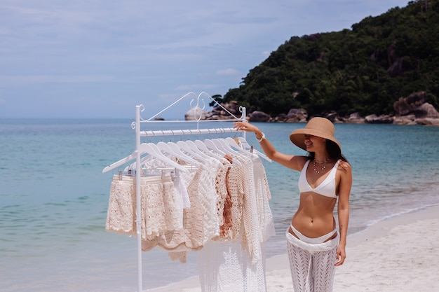 ビーチのハンガーからニットの服を選ぶ女性