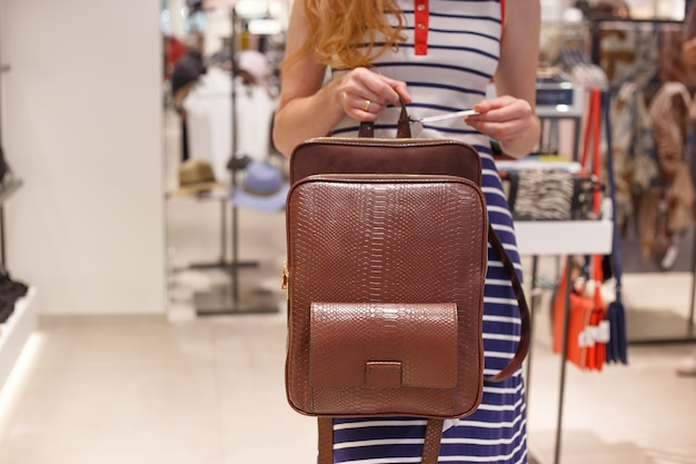 Woman choosing leather backpack at shop