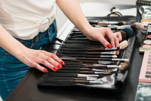 Woman choosing makeup brush from set