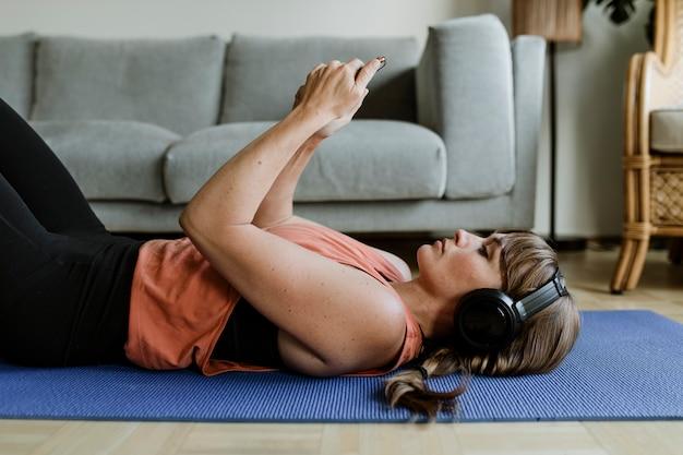 Женщина выбирает музыку со своего телефона, лежа на коврике для йоги во время карантина из-за коронавируса
