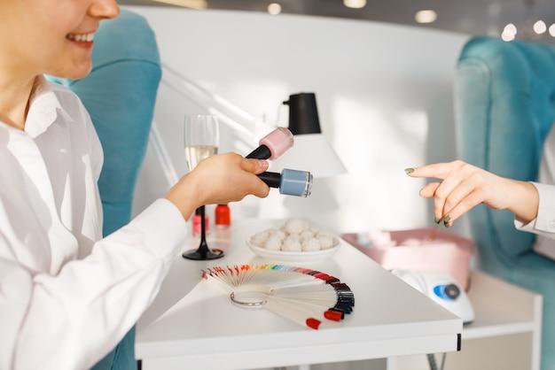 Woman choosing nail varnish in beauty salon, manicure and pedicure procedure.