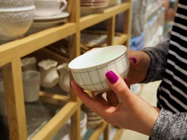 Woman choosing new crockery in dinnerware store