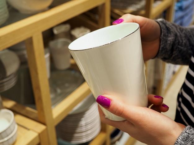 Женщина выбирает новую посуду в магазине посуды Premium Фотографии