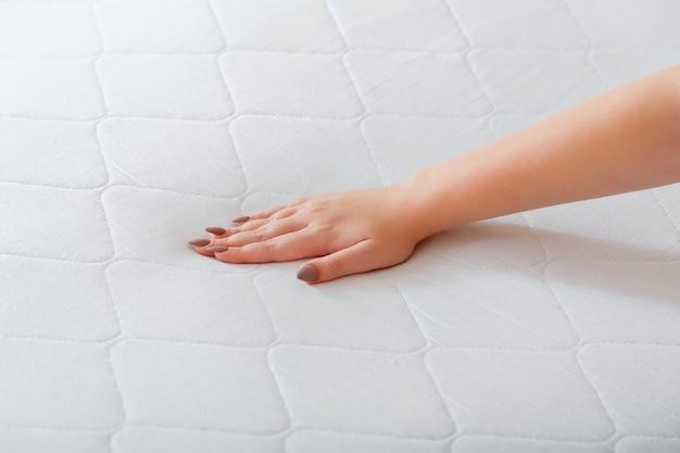 Woman choosing new mattress. female hand pressing testing mattress to check softness. choice comfortable mattress for sleep in store. quality control hardness of mattress materials orthopedic foam.