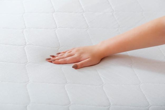 新しいマットレスを選ぶ女性。柔らかさをチェックするためにテストマットレスを押す女性の手。店内での睡眠に快適なマットレスをお選びください。マットレス材料の品質管理硬度整形外科用フォーム。