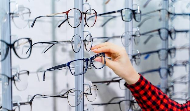 안경점에서 새 안경을 선택하는 여자. 광학. 안과학.