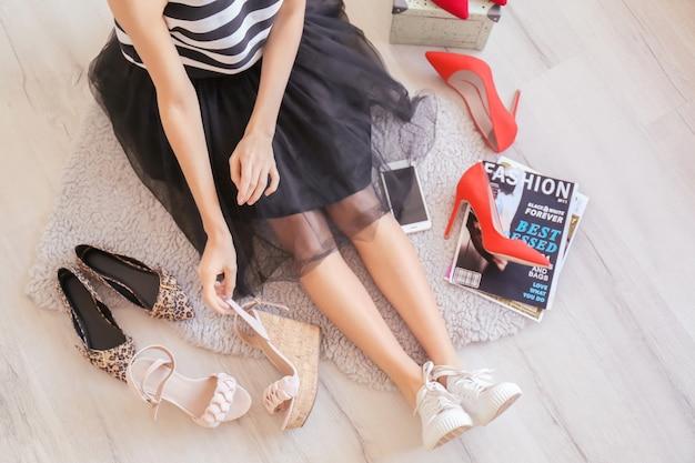室内で靴を選ぶ女性。スタイリッシュなワードローブ