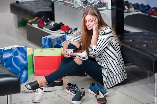Женщина, выбирающая обувь