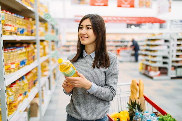 Woman choosing sunflower oil in a supermarket