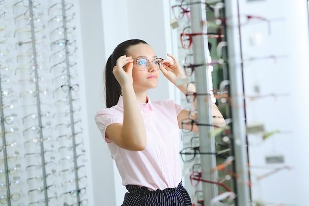 光学店、視力、視力の概念で眼鏡を選ぶ女性。