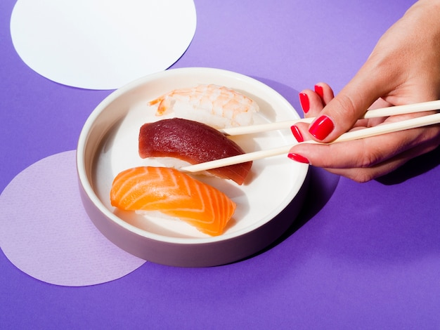 Woman choosing a tuna sushi from a white bowl