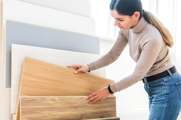 Woman choosing wood laminated flooring in shop