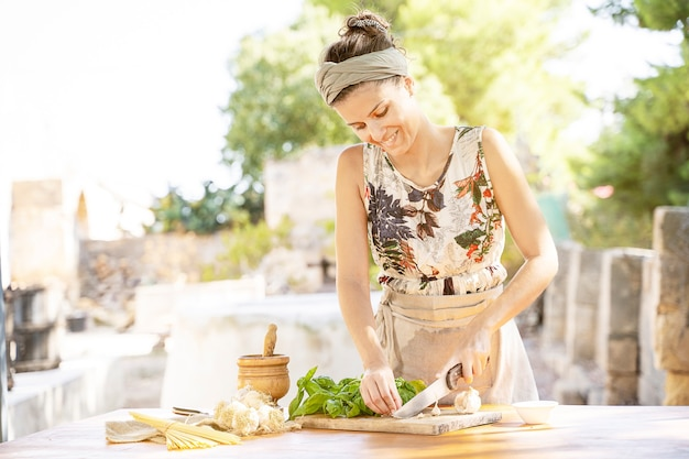 Woman chopping bunch of basil on a wooden cutting board outdoor