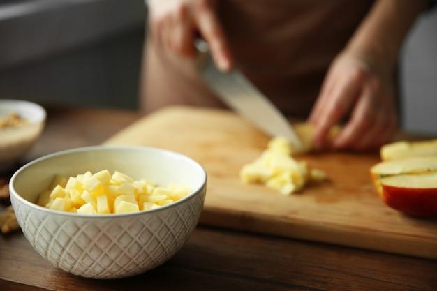 まな板の上で熟したリンゴを切り刻む女性