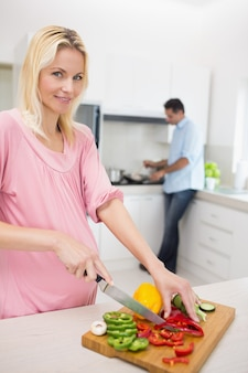 Woman chopping vegetables with man doing dishes at kitchen
