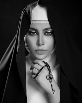 Woman in christian prayer outfits with a cross in dark space