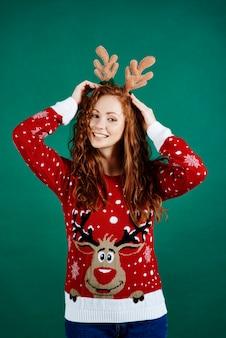 Donna in abiti natalizi sulla parete verde