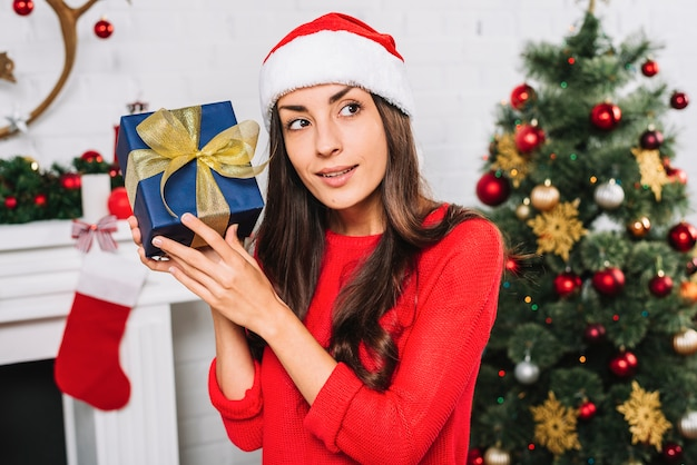 Woman in christmas hat holding present box