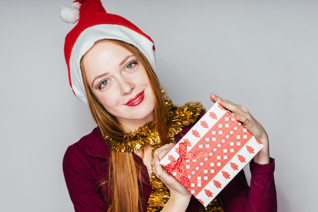 Woman in a christmas hat holds a gift in her hands