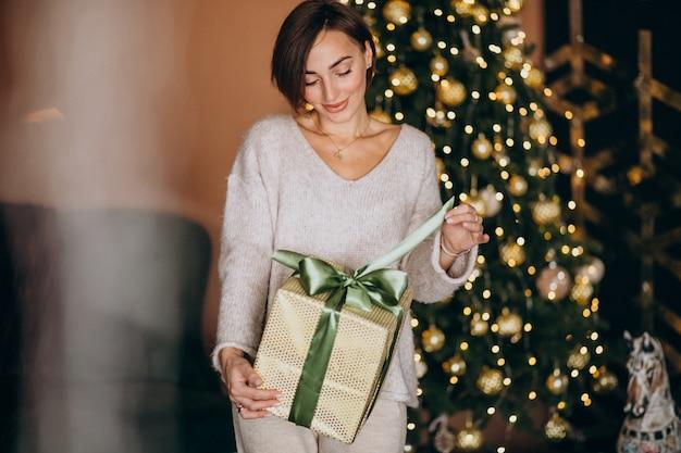 Woman on christmas holding a christmas present by the christmas tree