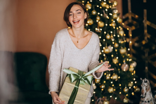 Woman on christmas holding a christmas present by the christmas tree