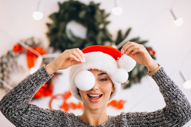 Woman on christmas holding christmas tree toys in front of her eyes