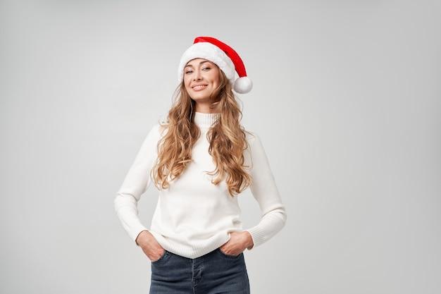 女性のクリスマスサンタ帽子セーター白いスタジオの背景