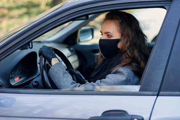 Woman in the city. person in a mask. coronavirus theme. woman by the car.