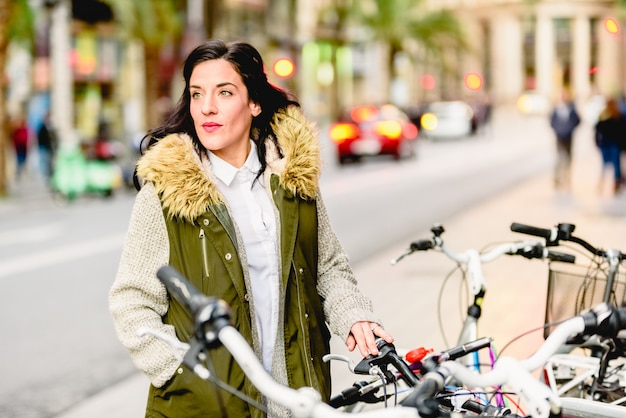 Woman in the city with her bicycle posing calm.