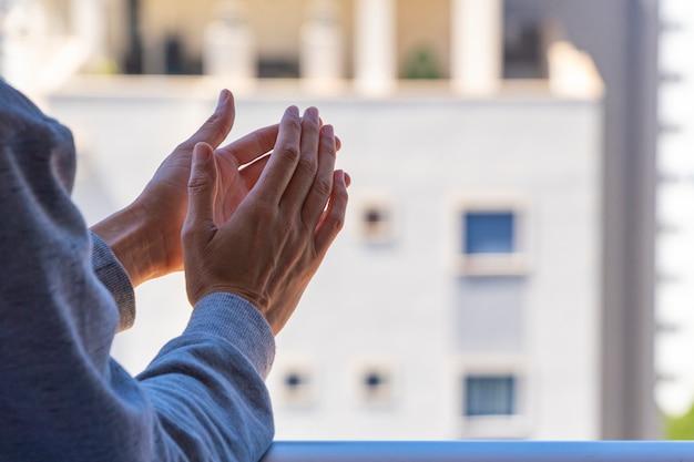 Женщина хлопает в ладоши, аплодирует с балкона