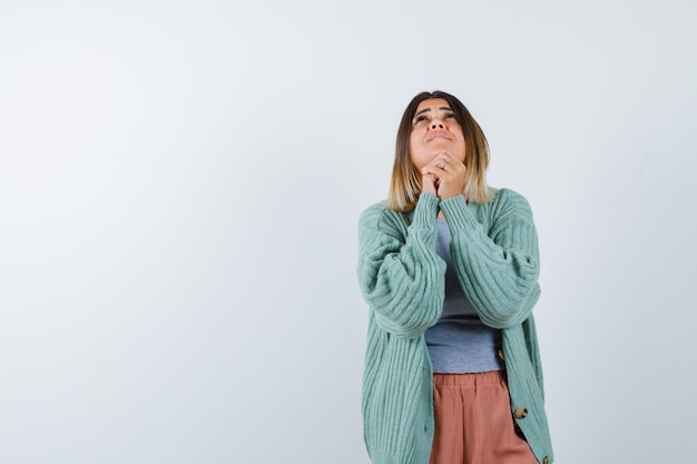 Woman clasping hands in praying gesture in casual clothes and looking hopeful. front view.