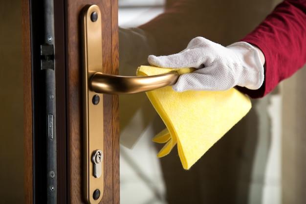 여자는 천으로 입구 문 손잡이를 청소합니다. 헝겊으로 표면을 소독하는 장갑을 끼십시오. 청소에 새로운 정상적인 covid 코로나 바이러스.