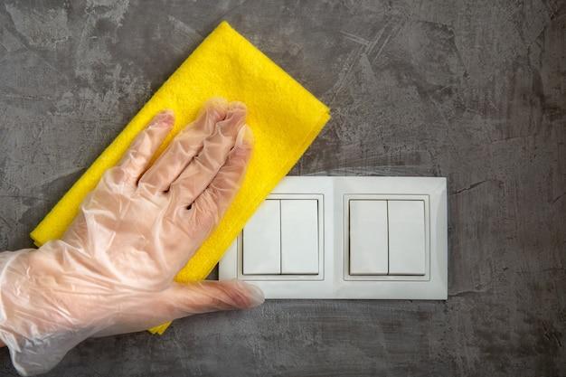 여자는 회색 콘크리트 벽에 천으로 전등 스위치를 청소합니다. 노란색 걸레로 표면을 소독하는 장갑을 끼십시오. 청소에 새로운 정상적인 covid 코로나 바이러스.