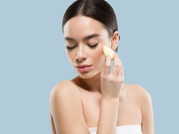 Woman clean skin with sponge beauty healthy skin beauty. color background. blue