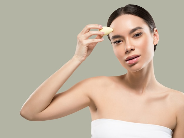 Woman clean skin with sponge beauty healthy skin beauty. color background. green
