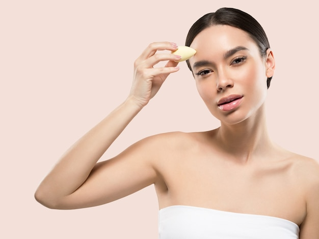 Woman clean skin with sponge beauty healthy skin beauty. color background. pink