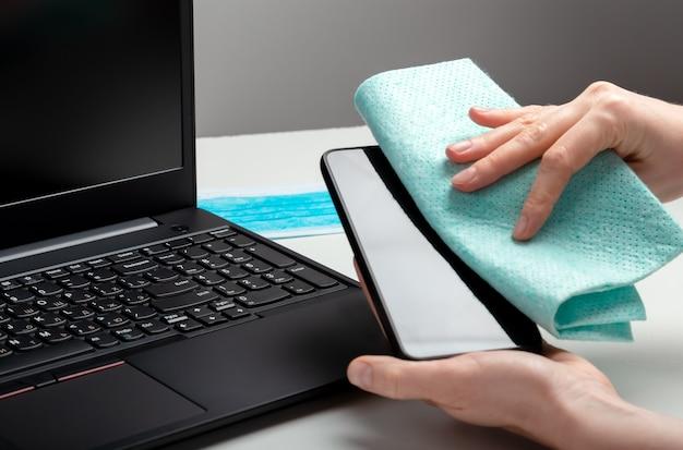 여성은 스마트폰 작업 공간을 청소합니다. 알코올 소독제로 홈과 노트북 키보드를 소독합니다. 여자 청소 직장 사무실 책상 표면입니다. new normal covid 19 코로나바이러스 위생.