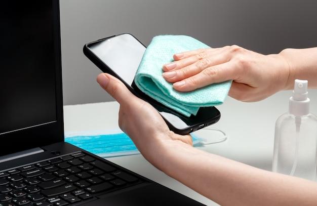 여자 깨끗한 스마트 폰 작업 공간. 알코올 소독제로 전화 및 노트북 키보드를 소독하십시오. 직장 사무실 책상 표면을 청소하는 여자. 새로운 정상적인 코로나 19 코로나 바이러스 위생.