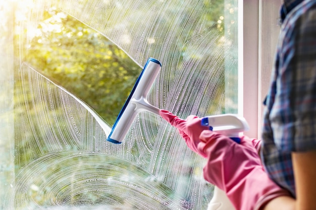 A woman clean a window pane with a squeegee and soap suds. cleaning with a detergent. hands in pink protective gloves washing glass on the windows with a spray bottle, home routine, housework concept.