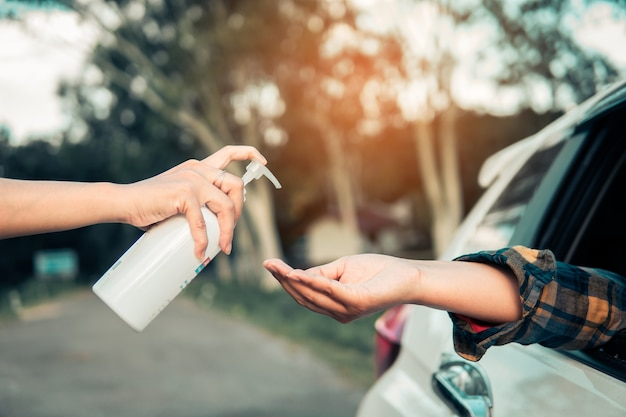 コロナウイルスやコビッド19を防ぐためにスクリーニングを行う前に75%アルコールジェルで手を掃除している女性