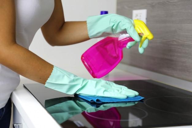 Женщина чистит современную черную индукционную плиту тряпкой и спреем.