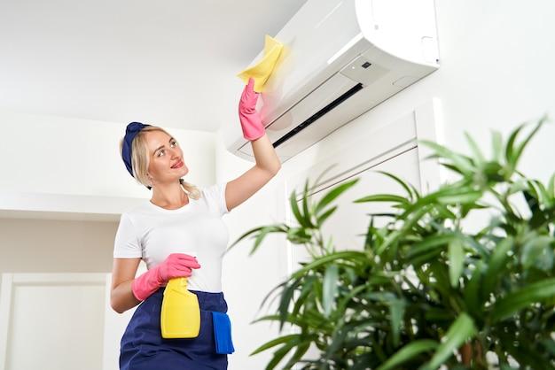 Женщина чистит кондиционер тряпкой. уборка или концепция домохозяйки