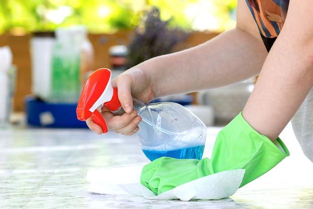 Женщина чистит и протирает стол