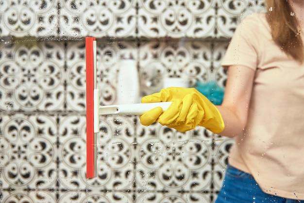 Женщина, чистящая кабину в ванной со скребком