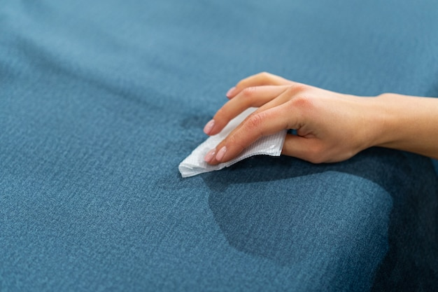 Woman cleaning a blue sofa with white cloth