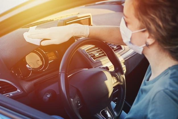 消毒スプレーで車のダッシュボードを掃除する女性