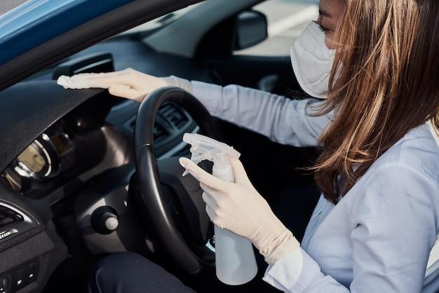 コロナウイルスから保護するために消毒スプレーで車のダッシュボードを掃除する女性。洗車