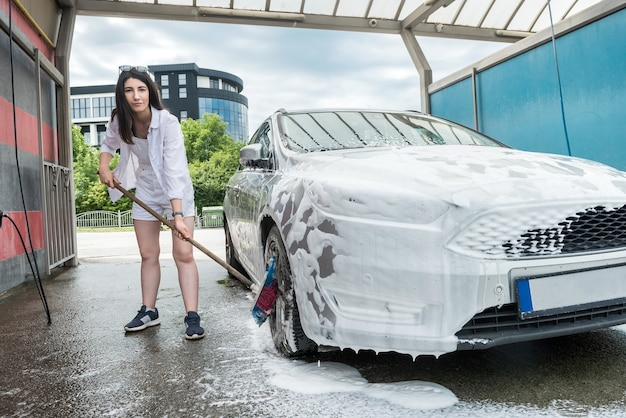 Woman cleaning car wheel  with brush and foam. cleaning concept