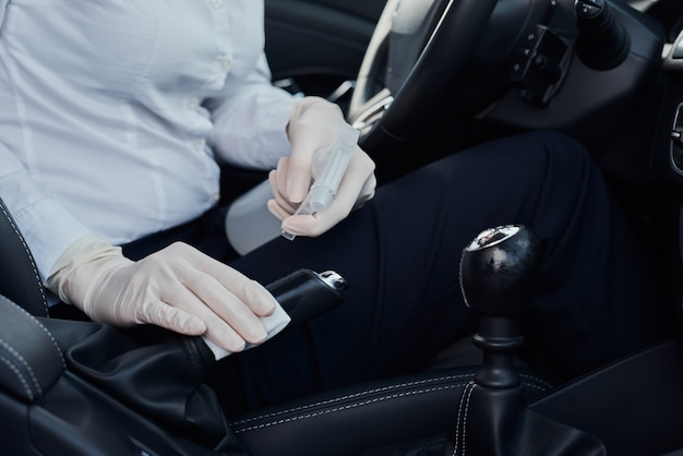 Woman cleaning car with disinfection spray to protect from coronavirus